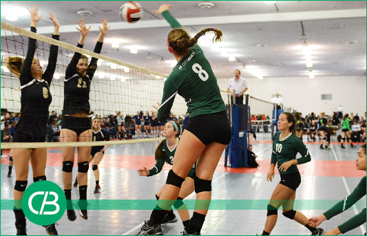 Girls volleyball team in green jersey spiking the ball